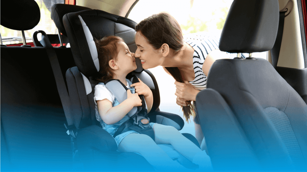 mother kissing baby in car seat